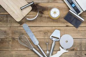Bakery and cooking tools with kitchen timer and scales on a wood table photo