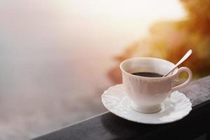 Morning coffee on a balcony with a sunrise and sun rays photo