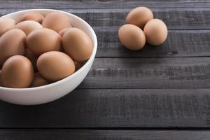 Chicken eggs in a white bowl and three chicken eggs outside on a black wooden table photo
