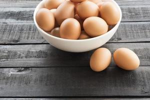 Chicken eggs in a white bowl and chicken eggs outside on a black wooden table photo