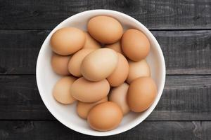 Fresh chicken eggs in a white bowl on a black wooden table photo