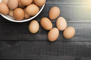 Fresh chicken eggs in a white bowl and six eggs outside on a black wooden table photo