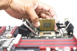 Hand holding a CPU and a motherboard socket for a CPU isolated on white background
