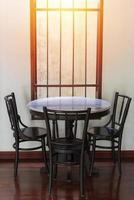 Wooden round table and chairs near a window with rays of sunlight on a wooden floor and white wall