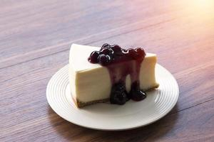 Blueberry cream cheesecake on a white plate on a wooden table