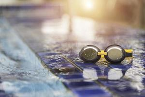 Goggles on the side of a swimming pool