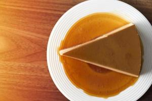 Homemade caramel custard pudding on a white plate on a wooden table