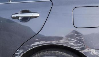 Scratches on the body of a gray car from an auto accident photo