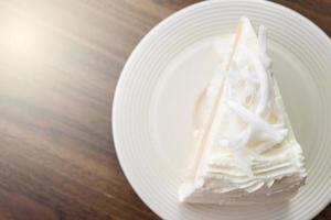 A piece of coconut cake on a white dish
