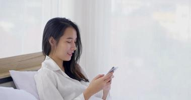 Young Asian Woman Typing on Her Phone