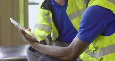 dois homens discutindo estratégia usando um tablet no trabalho