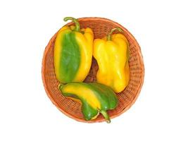 Yellow and green bell peppers in a wicker bowl on a white background