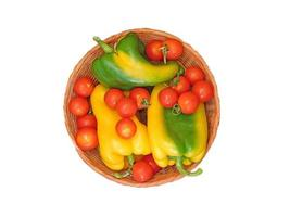 Tomatoes and yellow and green bell peppers in a wicker bowl on a white background