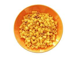 Tube pasta in an orange bowl isolated on a white background photo