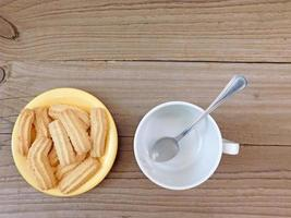 Cookies on a yellow plate next to empty coffee cup on a wooden table background photo