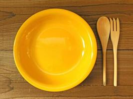 Yellow bowl with wooden fork and spoon on a wooden table background photo