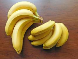 Racimo de plátanos sobre un fondo de mesa de madera foto