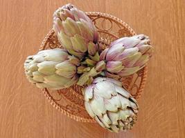 Alcachofas en un recipiente de mimbre sobre un fondo de mesa de madera foto