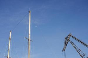 Boat masts and a crane against a blue sky with the moon