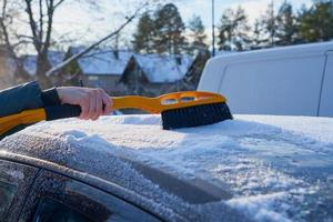 Removing snow from the roof of a car photo