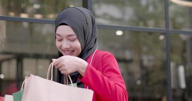 mulher muçulmana sorrindo enquanto faz compras video