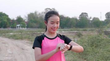 Asian Woman Setting Her Smartphone Before a Run video
