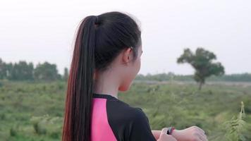 Asian Woman Sets Her Smartwatch Before a Run Outside