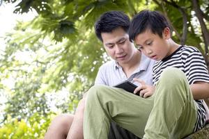 Father and son reading outside