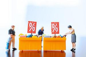 Miniature shoppers with a discount tray for shopping discounted items photo