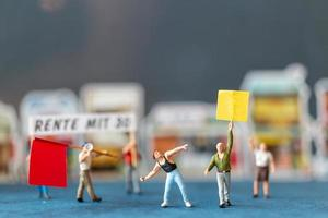 Miniature people, protesters holding signs, raising their hands for revolution, protesting concept
