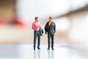Miniature businessmen standing on empty space for text photo