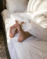 Feet of a sleeping person sticking out from under a warm and comfortable blanket on the bed, bare heels