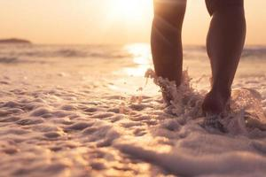 Feet walking slowly, life and relaxation on a sandy tropical beach with a blue sky background