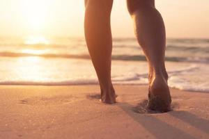Pies caminando lentamente, vida y relajación en una playa tropical de arena con un fondo de cielo azul foto