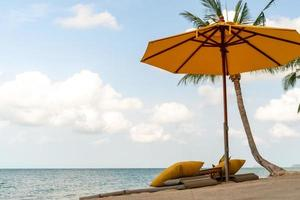Umbrella and chair at a tropical summer beach background with copy space blue sky