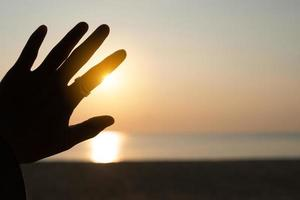 Hand reaching out to a sunset sky beach sand nature background