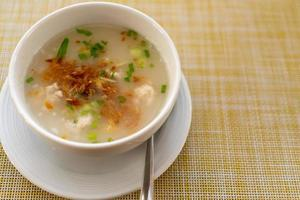 Thai-style breakfast pork rice soup with egg on a wooden table