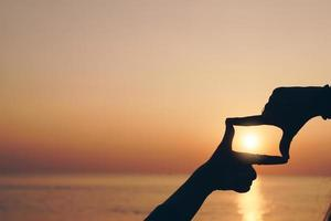 Selective focus of woman's hands making a frame with a finger gesture with sunset or sunrise, female capture sunrise or sunlight outdoors, future planning concept.