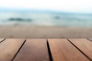 Selective focus of old wood table with blur beautiful beach background for display