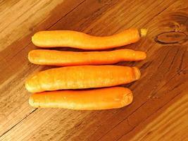 Cuatro zanahorias enteras en una mesa de madera foto