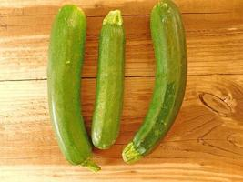 Three whole zucchini on a wooden tabletop background