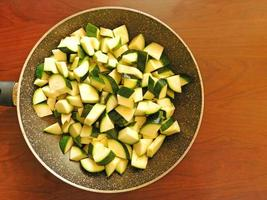 Diced zucchini in a pan on a wooden tabletop background