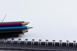 Cuaderno en blanco aislado con lápices de colores foto