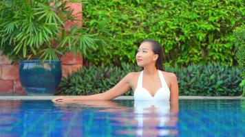 Asian Woman Relaxes Around Pool in Resort on A Nice Day video