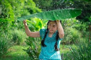 Mujer asiática sosteniendo una hoja de plátano bajo la lluvia foto