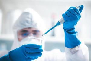 Researcher adding liquid to a beaker