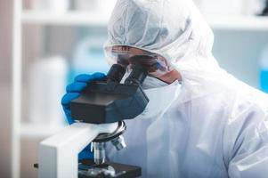 Researcher looking into a microscope