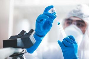 investigador extrayendo una vacuna covid-19 de un vil foto
