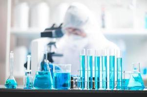 Equipo de laboratorio con investigador al fondo. foto