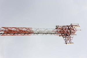 Telecommunication tower in a cloudy sky background